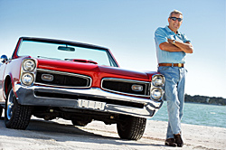 Photo of man standing beside a classic car